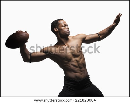 Bare chested football player throwing football - stock photo