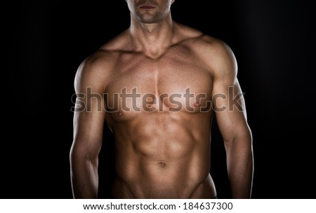Bare chested muscular man on dark background.