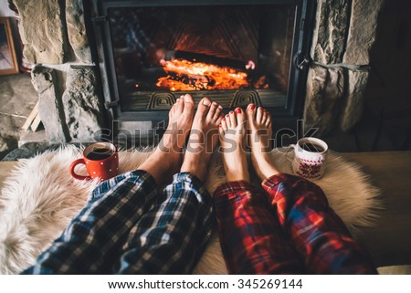 Bare couple feet by the cozy fireplace. Man and Woman relaxes by warm fire with a cup of hot drink and warming up her feet. Close up on feet. Winter and Christmas holidays concept. - stock photo