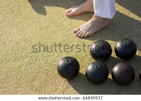 Bare Feet And Bowling Balls On A Lawn Bowls Green - stock photo