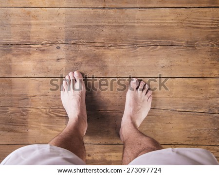 Bare feet of a runner on a wooden floor background - stock photo