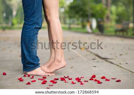 Bare feet of lovers among rose petals  - stock photo
