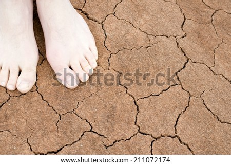Bare feet on cracked earth - stock photo