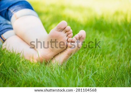 bare feet on spring grass  - stock photo