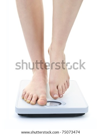 Bare female feet standing on bathroom scale - stock photo