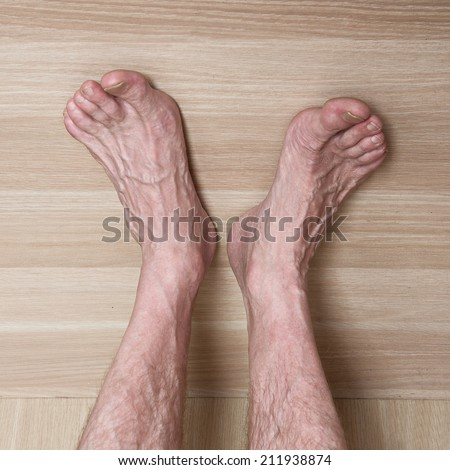 bare hairy man's feet on the wooden light beige background - stock photo