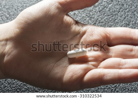 Bare hand holding one white medicinal tablet - stock photo