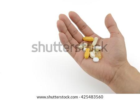 Bare hand of patient preparing medicine and vitamin to take. - stock photo
