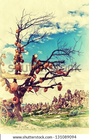 Bare tree with crocks on the branches in beautiful Cappadocia mountains. Retro style photo. - stock photo