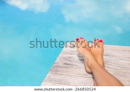 Bare woman feet on wooden deck by the swimming pool - stock photo