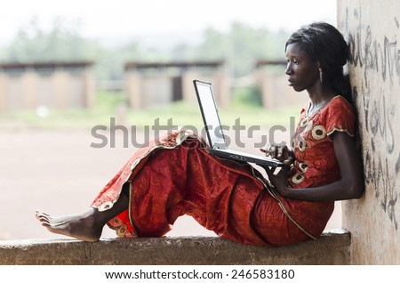 Barefoot African Model Working On Her Laptop Computer Business Symbol  - stock photo
