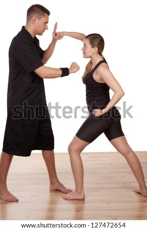 Barefoot athletic young woman and man practising kick boxing blocking and throwing punches as they train together - stock photo