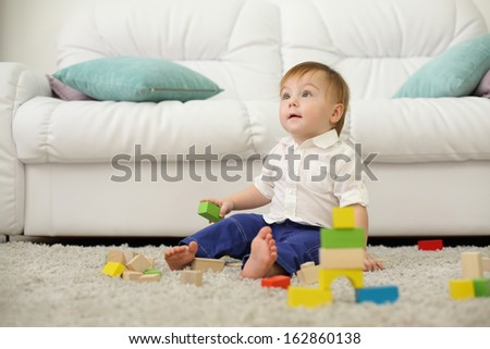 Barefoot baby sits on carpet with wooden cubes and looks up near sofa. Shallow depth of field. - stock photo