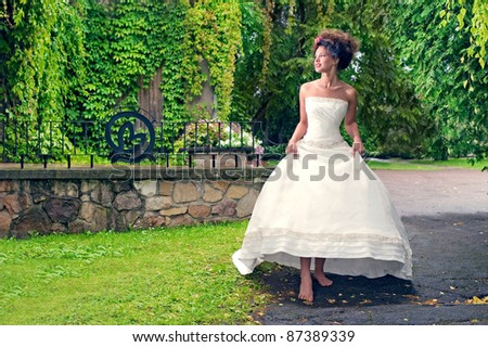barefoot bride walks in the park in the rain