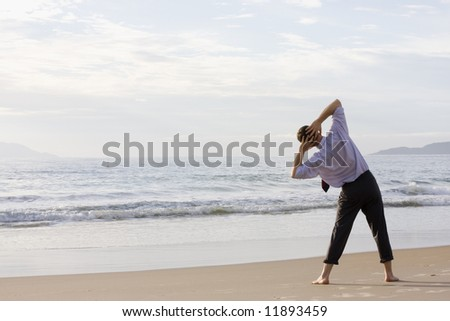 Barefoot businessman doing exercises on a tropical beach - stock photo