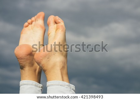 Barefoot female feet in the beach sand on a sky background