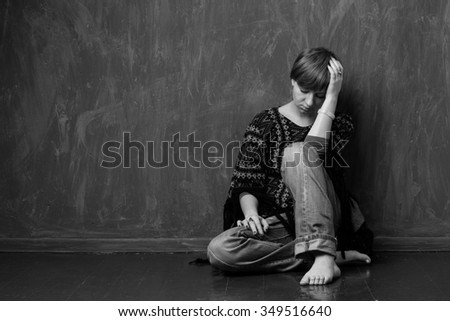 Barefoot girl is sitting bowed head on the floor against the wall. Black and white. - stock photo