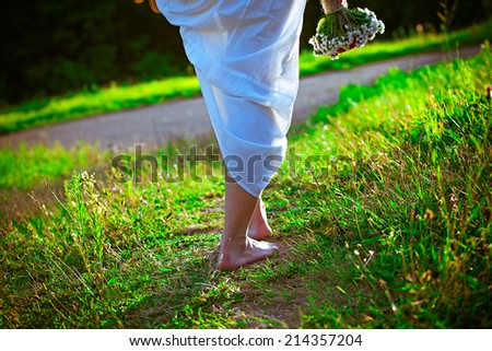 Barefoot girl walk in the park - stock photo