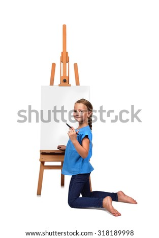 barefoot little girl artist drawing on easel - stock photo