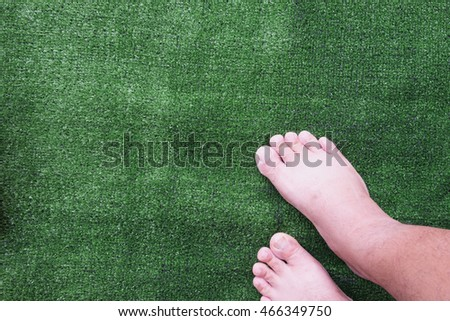 Barefoot on green artificial grass field