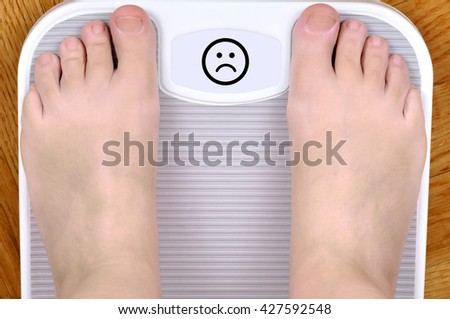 Barefoot person standing on the weight scale. The scale shows bad smiley - stock photo