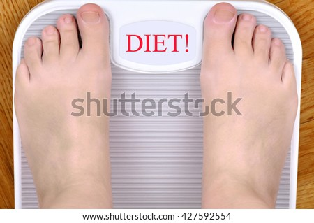 Barefoot person standing on the weight scale. The scale shows DIET! - stock photo