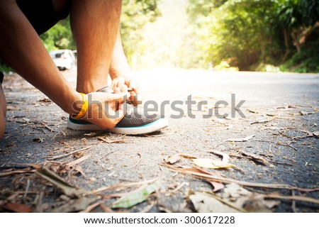 Barefoot running shoes closeup. man athlete tying laces for jogging on road in minimalistic barefoot running shoes. Runner getting ready for training. Sport lifestyle. - stock photo