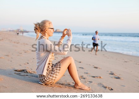 Barefoot smiling girl in glasses sitting on sand beach and taking pictures by smartphone in sunrise - stock photo