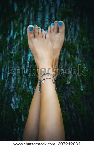 barefoot woman feet with ankle bracelets lean on tree with moss, natural light, selective focus