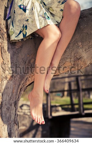 barefoot woman legs, sit on tree in romantic summer dress - stock photo
