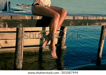 barefoot woman sit on sea dock relaxing summer day at sunset - stock photo