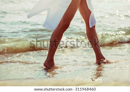 barefoot woman walk through sea water on sandy beach in white long shirt, lower body, selective focus, side view