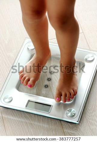Barefoot woman with manicured toenails standing on a modern glass electronic bathroom scale as she checks her weight, close up high angle view of her legs