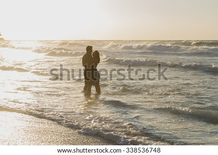 Barefoot young couple, the woman in a blue dress, and the man in shorts, enjoys a romantic walk on a sandy beach in a late summer hazy day, at dusk. - stock photo