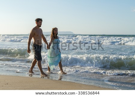 Barefoot young couple, the woman in a long turquoise dress, and the man in shorts, enjoys a romantic walk on a sandy beach in a late summer hazy day, at dusk.