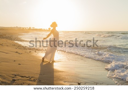 Barefoot young woman in a long white dress enjoys a lonesome walk on a sandy beach in a late summer hazy day, at dusk.
