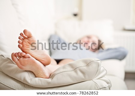 Barefoot young woman lying on sofa, shallow depth of field, focus on foot soles - stock photo
