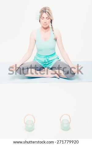 Barefoot young woman with her blond hair in a pigtail sitting in the lotus position on a mat meditating with her eyes closed and a tranquil expression - stock photo