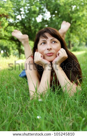 barefooted caucasian brunette woman lying in grass enjoying and dreaming
