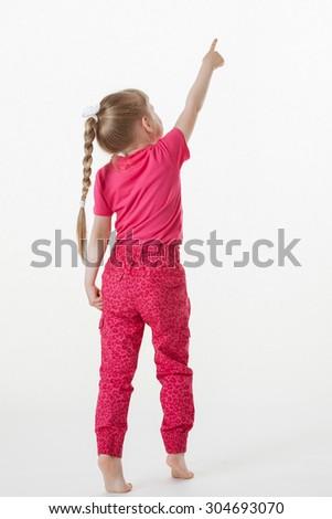 Barefooted little girl turning back and indicating something up, white background - stock photo