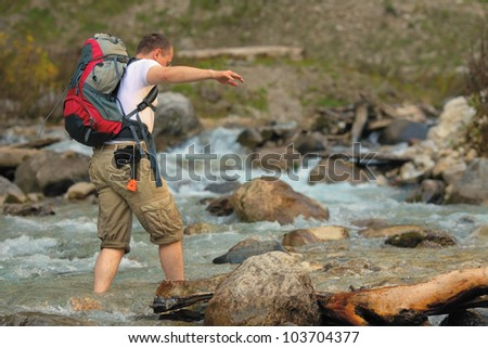 Barefooted tourist crossing mountain river