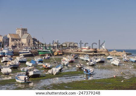 BARFLEUR, FRANCE - JULY 3, 2011: Fishing and recreational boats at low tide in the harbor of Barfleur. Barfleur is a picturesque fishing village in Basse Normandy.