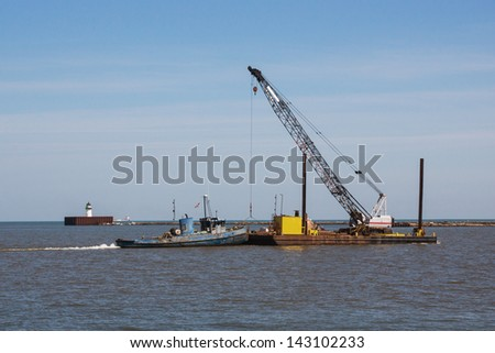 Barge And Crane:  A small tugboat pushes a construction crane sitting on a barge across the harbor at Cleveland, Ohio
