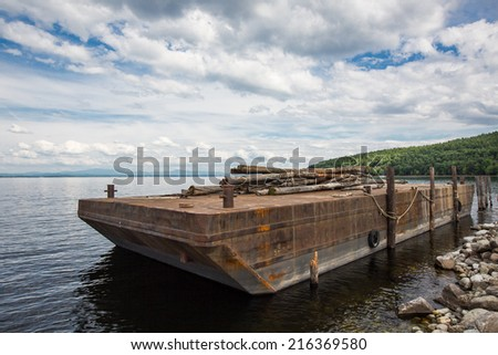 Barge carrying wood logs - stock photo