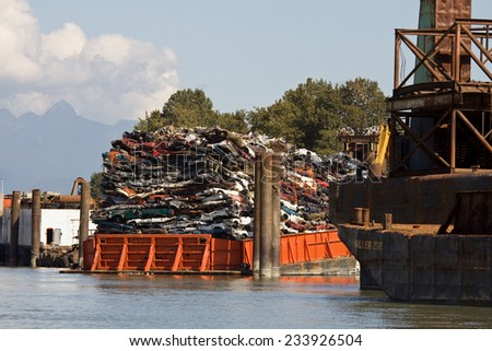 Barge filled with crushed cars, for recycling, along the Fraser River in Surrey, BC - stock photo