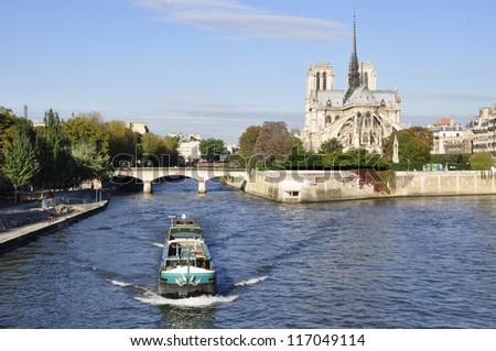 Barge on river Seine as it passes near Notre-Dame, Paris - stock photo