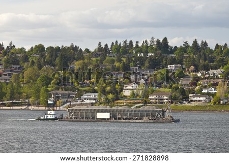 Barge passes by new mansions looking over the columbia river from Washington state. - stock photo