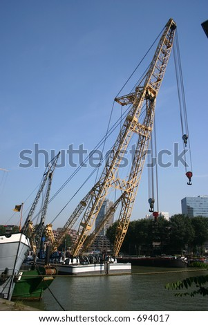 Barges, with crane outlined against blue sky& city background , for offloading - stock photo