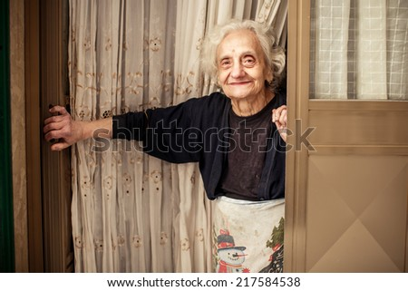 BARI, ITALY - NOVEMBER 2, 2013: Old woman looking out of the door in Bari on November 2, 2013, Italy - stock photo