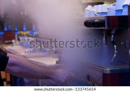 Barista bartender preparing drinks on coffee machine with shallow depth of field